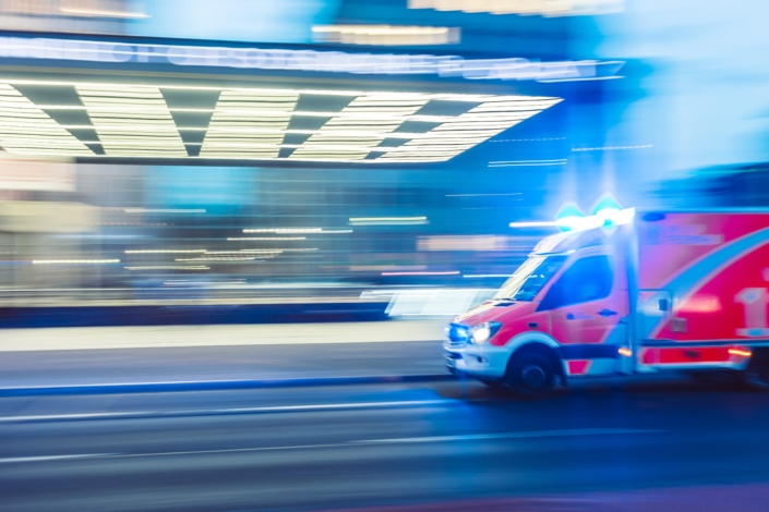 ambulance driving along a road with intense blue lights